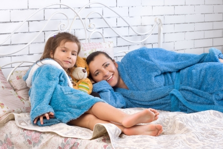 woman bathrobe: Mother and her five year old daughter are in robes on the bed