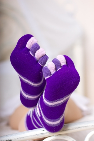 Female legs in purple socks with individual toes Stock Photo