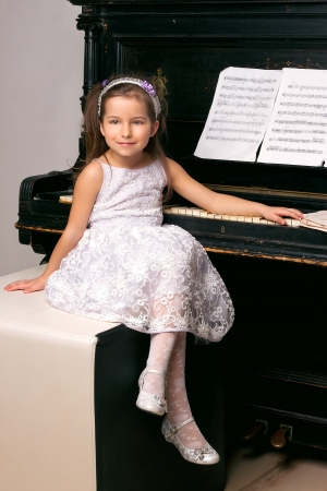 5 year old girl in a black dress sitting near the piano Stock Photo