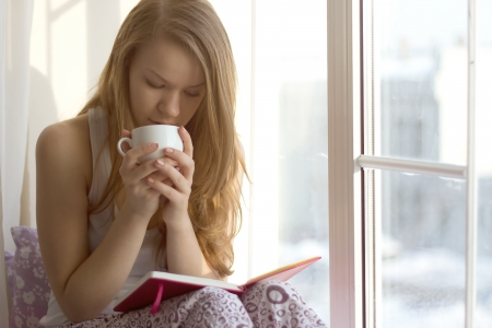 warm house: Girl near the window in the morning drinking tea