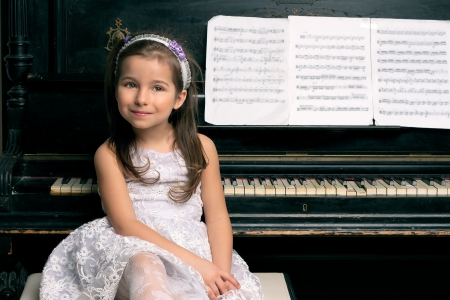 five year old: Cute five year old girl sitting by the piano black