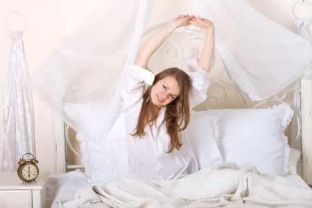 nice caucasian girl stretching on a bed on a light background