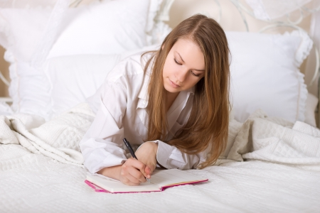 Girl writes a diary while lying in bed in the morning Stock Photo