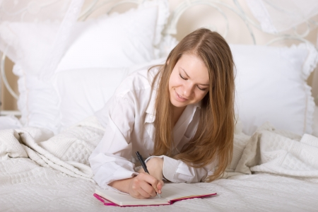 Girl writes a diary while lying in bed in the morning Standard-Bild