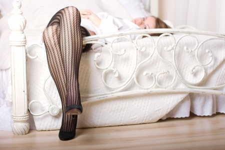 Attractive legs on white bed with fishnet stockings and high heel shoes.