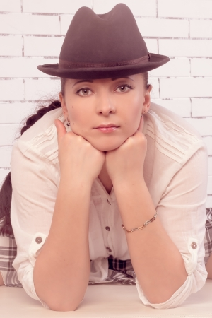 30 year old: Large portrait of 30 year old woman in a hat, leaning on the face with his fists, vintage treatment Stock Photo