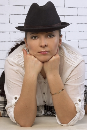 30 year old: Large portrait of 30 year old woman in a hat, leaning on the face with his fists