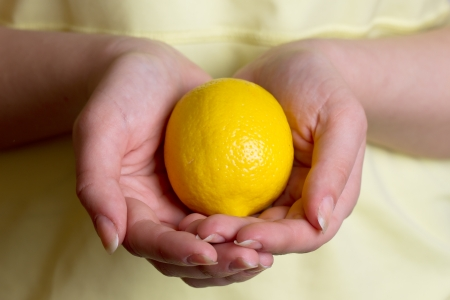 girl in a yellow dress holding a lemon with two hands on a white background Stock Photo