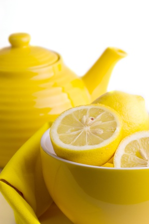 Yellow lemons in a bowl near the teapot, truncating
