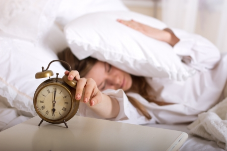 Alarm clock on table and woman sleeping in background photo