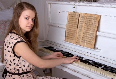 beautiful young woman playing the piano photo