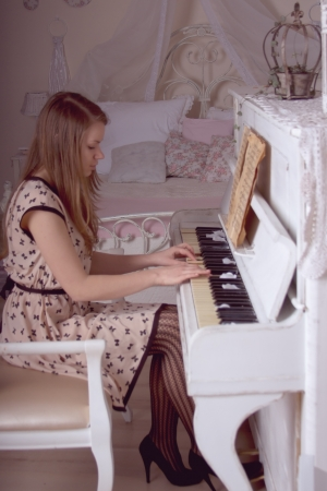 beautiful young woman playing the piano photo