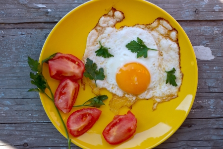 Scrambled eggs with tomato in a yellow plate on the old board photo