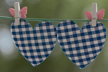 string together: blue heart attached to a clothesline with pin