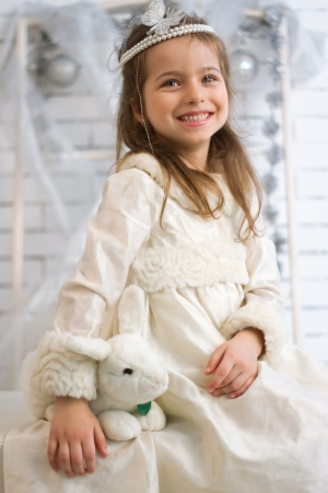Girl in winter holiday dress with a toy rabbit Stock Photo - 21882007