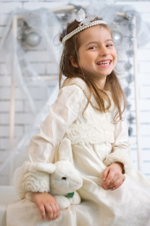 Girl in winter holiday dress with a toy rabbit Stock Photo - 21882008