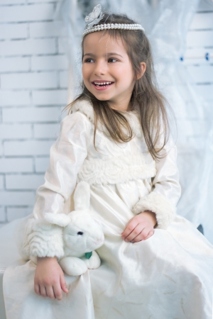Girl in winter holiday dress with a toy rabbit Stock Photo - 21847378