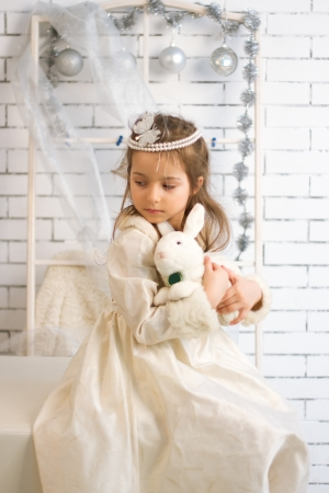 Girl in winter holiday dress with a toy rabbit Stock Photo - 21882013