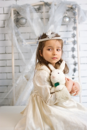 Girl in winter holiday dress with a toy rabbit Stock Photo - 21882014