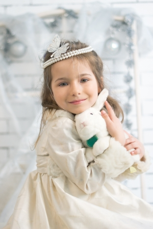 Girl in winter holiday dress with a toy rabbit Stock Photo - 21882020