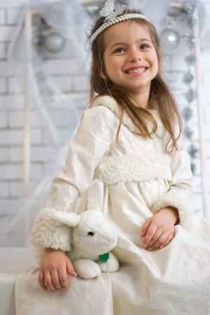 Girl in winter holiday dress with a toy rabbit photo