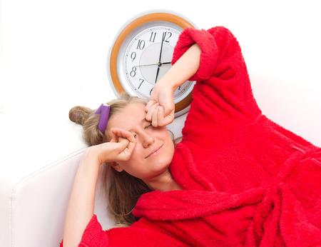 wellness sleepy: sleepy woman with a clock yawning over white background Stock Photo