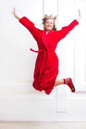 red bathrobe: woman in a red bathrobe jumping joyfully Stock Photo