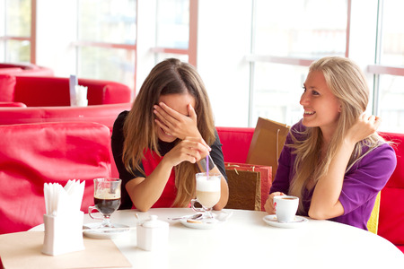 Two beautiful and elegant woman sitting in cafeFriends drink coffee photo