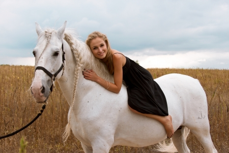 horse blonde: girl in the black dress is riding on a white horse