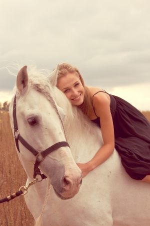 beautiful young woman with a  horse in the forest photo