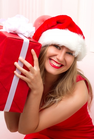 Christmas Santa hat woman portrait hold christmas gift. Smiling happy girl on white background. photo