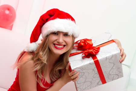 Christmas Santa hat woman portrait hold christmas gift. Smiling happy girl on white background.