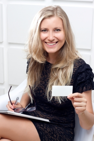 Portrait of smiling business woman giving blank business card photo
