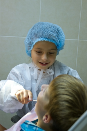 A couple of kids playing doctor at the dentist photo