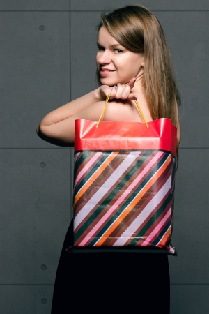 beautiful young woman with colored shopping bags over blue background photo