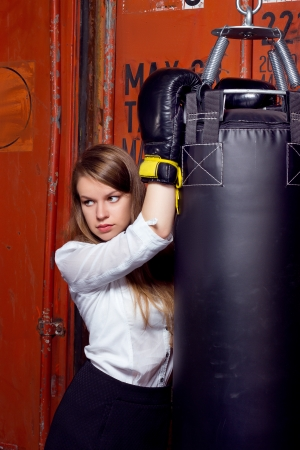 Girl in a business suit near punch bag photo