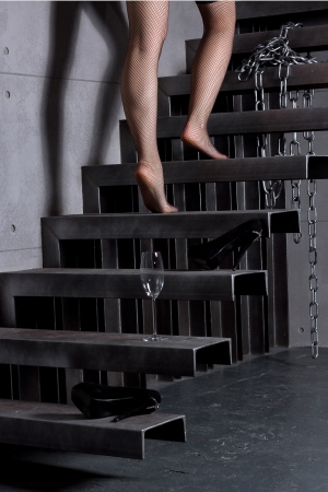 Woman skirt going up the stairs at home, holding glass
