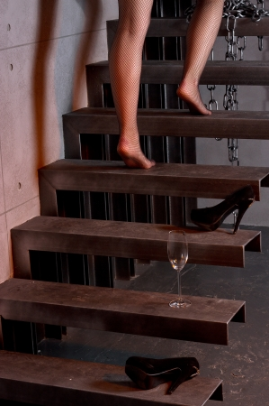 Woman going up the stairs at home, holding glass