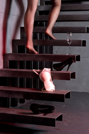 Woman going up the stairs at home, holding bras and glass in hand.