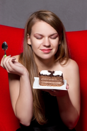 girl with pleasure eats chocolate cake photo