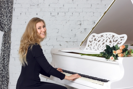 beautiful young woman playing the white piano photo