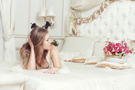in love with a beautiful young girl lying in bed, strewn with roses. Feast day of St. Valentine Stock Photo - 23379420