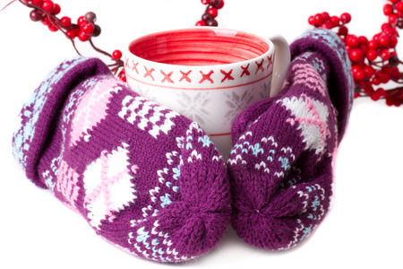Cozy red gloves hold a mug of hot cocoa photo