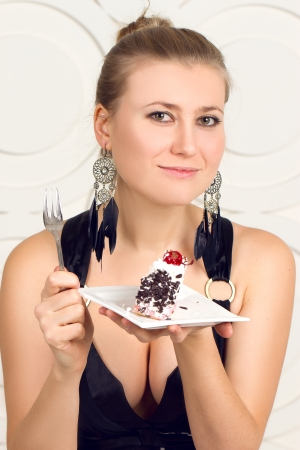 Young beautiful woman eating  chocolate cake  photo