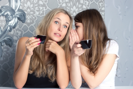 Two girls girlfriends fissile secrets over coffee Stock Photo
