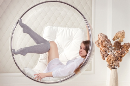 tunic: Girl in white tunic sitting in a chair suspended round