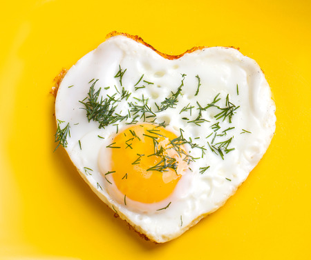 Breakfast. Fried eggs in a heart shape with dill photo