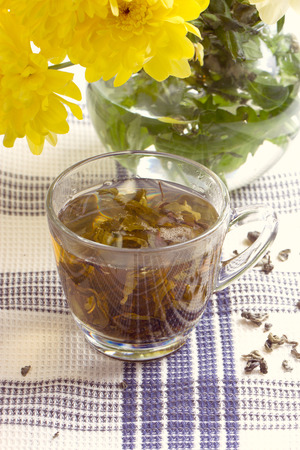 Herbal tea in glass cup and flowers on wooden table photo
