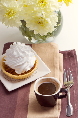 Coffee and cake with whipped cream near chrysanthemums photo