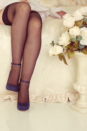 fishnet stockings: Attractive legs on white bed with fishnet stockings and high heel shoes.
